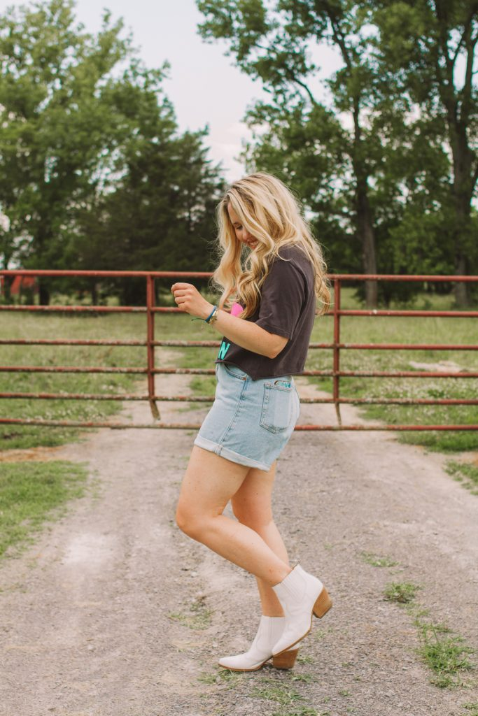 The Best of Denim Shorts for Thick Thighs featured by top Nashville fashion blogger, Pearls and Twirls: image of a woman wearing Topshop rolled hem denim shorts