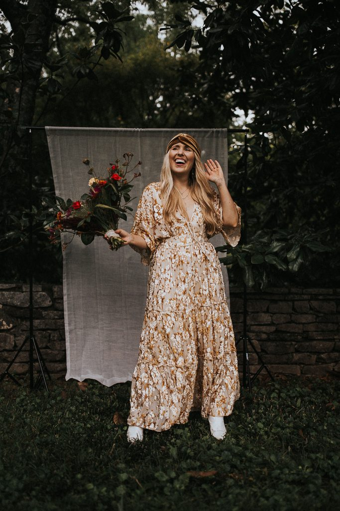Being Creative by popular Nashville lifestyle blog, Pearls and Twirls: image of a woman holding a bouquet of flowers and wearing a gold velvet head wrap and white and gold floral dress.