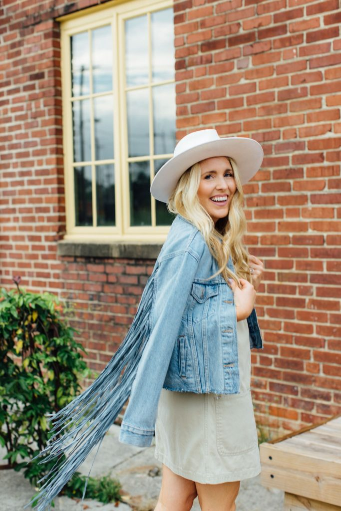 steps to simplify your life | Simplify Your Life by popular Tennessee lifestyle blog, Pearls and Twirls: image of a woman standing in front of a brick building and wearing a tan jumper, fringe denim jacket and cream fedora hat.