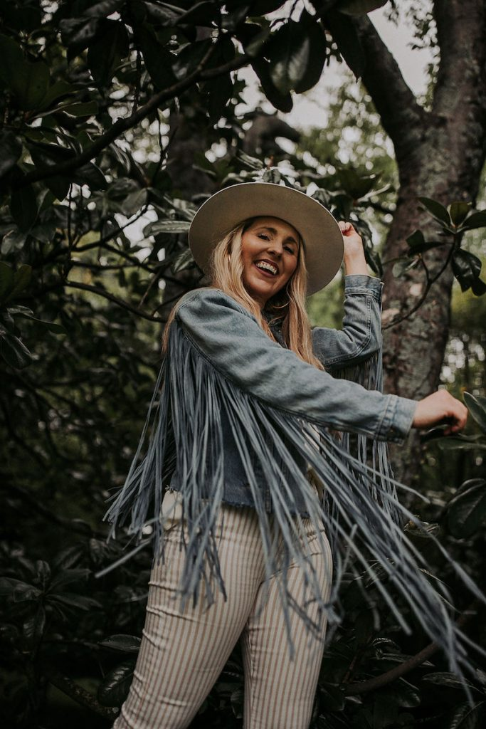 Nuuly Review by popular Nashville fashion blog, Pearls and Twirls: image of a woman wearing a denim fringe jacket and tan and white stripe pants.