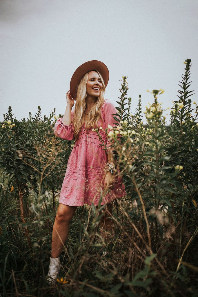 Nuuly Review by popular Nashville fashion blog, Pearls and Twirls: image of a woman wearing a pink dress, white boots, and a felt hat.