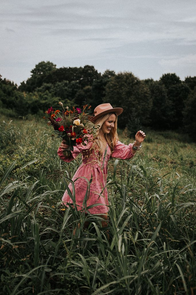 Monthly Goal by popular Nashville lifestyle blog, Pearls and Twirls: image of a woman standing in a field of yellow flowers and wearing a Free People Sweet Surrender Denim Mini Dress and felt fedora hat and holding a bouquet of various pink flowers.
