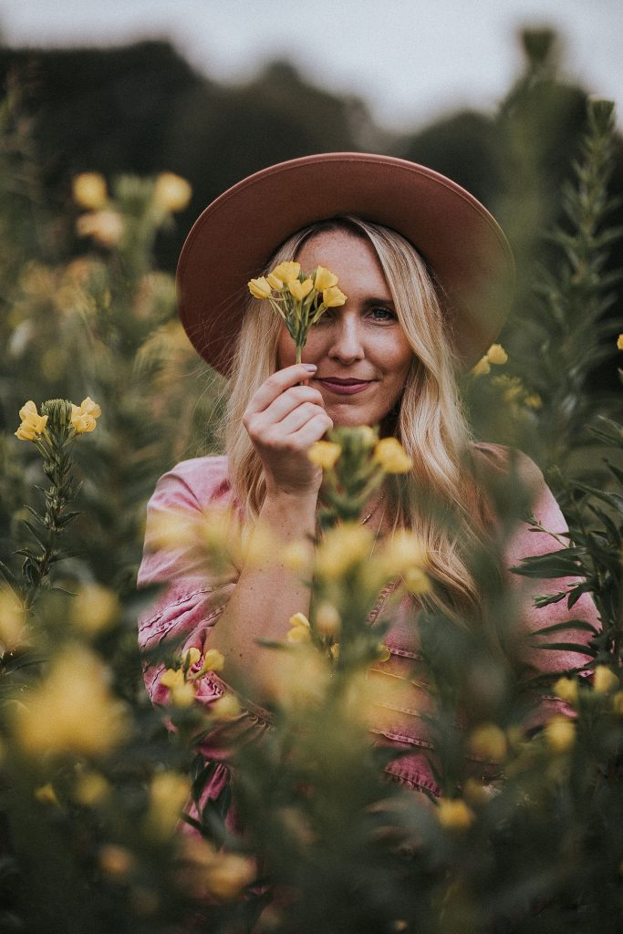 Monthly Goal by popular Nashville lifestyle blog, Pearls and Twirls: image of a woman standing in a field of yellow flowers and wearing a Free People Sweet Surrender Denim Mini Dress and felt fedora hat.