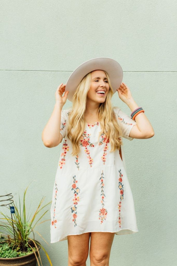 Consignment Sale by popular Nashville fashion blog, Pearls and Twirls: image of a woman wearing a mini floral embroidered dress, and fedora hat and standing in front of a stucco wall.