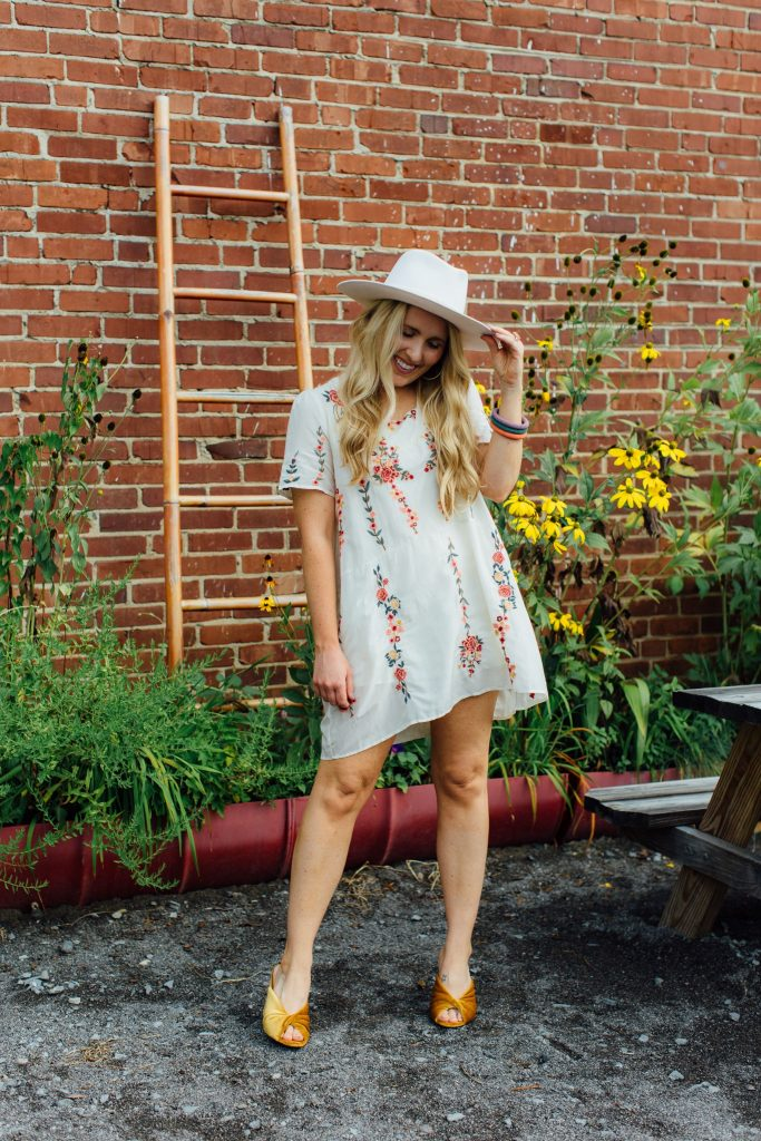Consignment Sale by popular Nashville fashion blog, Pearls and Twirls: image of a woman wearing a mini floral embroidered dress, velvet sling back peep toe shoes, and fedora hat and standing in front of a brick wall