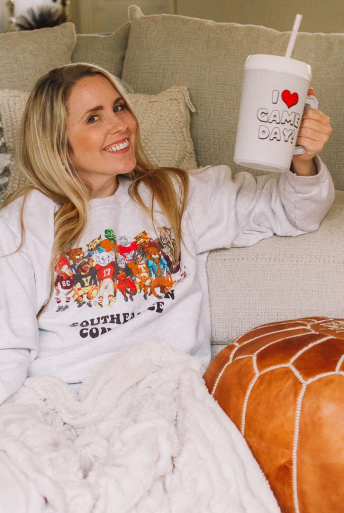 SEC Gameday by popular Nashville fashion blog, Pearls and Twirls: image of a woman wearing a My Kind of Lovely SEC Family Gameday sweatshirt and holding a I love Game Day mug.