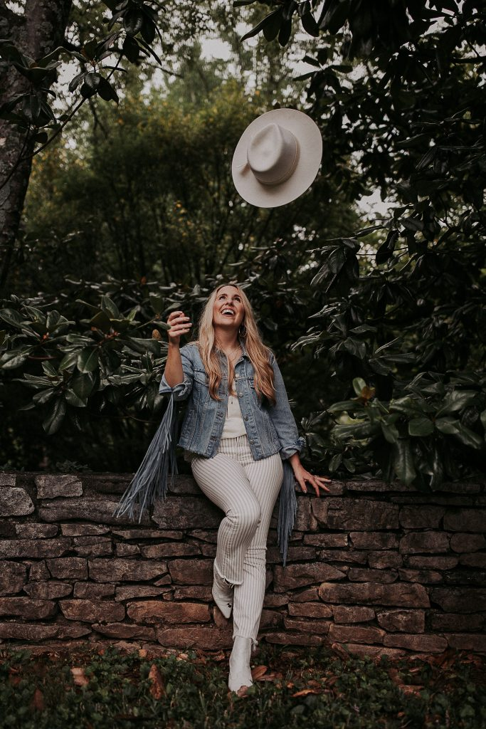 how to be more consistent | Being Consistent by popular Nashville lifestyle blog, Pearls and Twirls: image of a woman wearing a fringe denim jacket, white and blue stripe pants, white top, white boots and tossing a white rancher hat into the air.