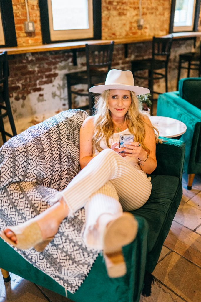 how to have a great monday | Have a Great Monday by popular Nashville lifestyle blog, Pearls and Twirls: image of a woman wearing tan and white striped pants, white tank top, white felt hat, and suede block heel sandals and sitting on a teal velvet couch.