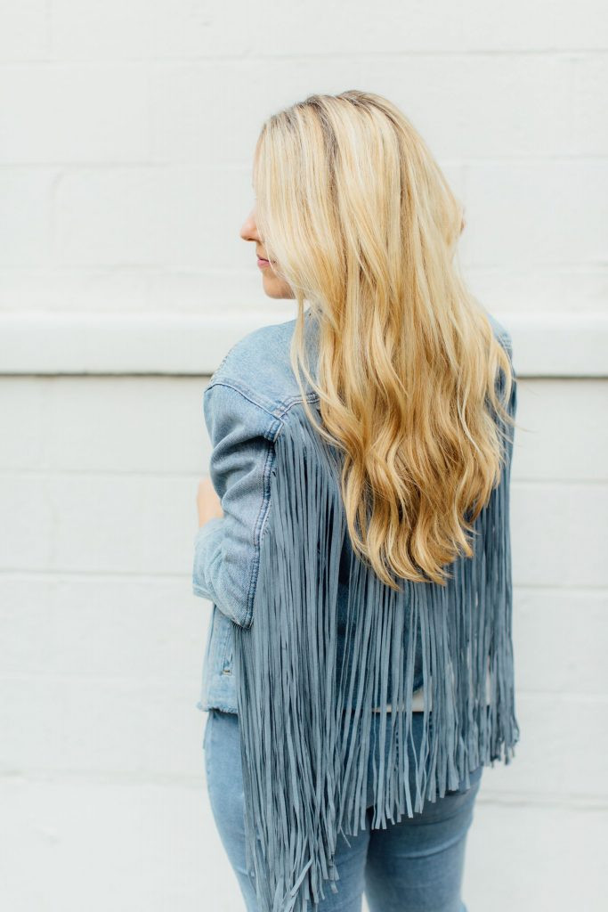 Winter Hair Care by popular Nashville beauty blog, Pearls and Twirls: image of a woman with long blonde hair wearing a fringed denim jacket.