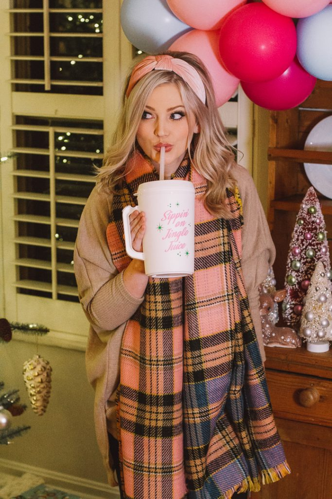 My Kind of Lovely Christmas |My Kind of Lovely by popular Nashville fashion blog, Pearls and Twirls: image of a woman drinking from a reusable Christmas mug and wearing a My Kind of Lovely Pink Tartan scarf.