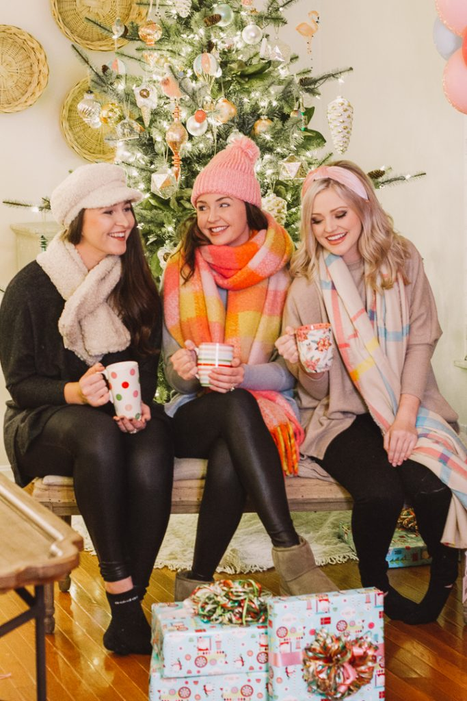 My Kind of Lovely Christmas |My Kind of Lovely Christmas |My Kind of Lovely by popular Nashville fashion blog, Pearls and Twirls: image of three women sitting in front of a Christmas tree and wearing My Kind of Lovely cold weather accessories.