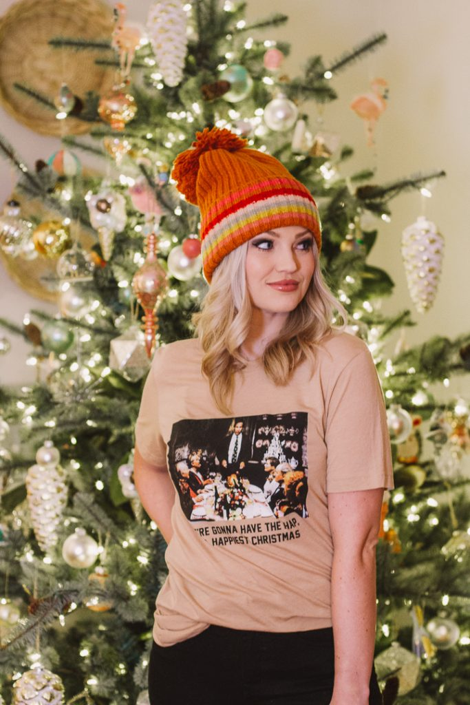 My Kind of Lovely Christmas tee | My Kind of Lovely by popular Nashville fashion blog, Pearls and Twirls: image of a woman standing in front of a Christmas tree and wearing a pom beanie and a My Kind of Lovely Christmas tee.