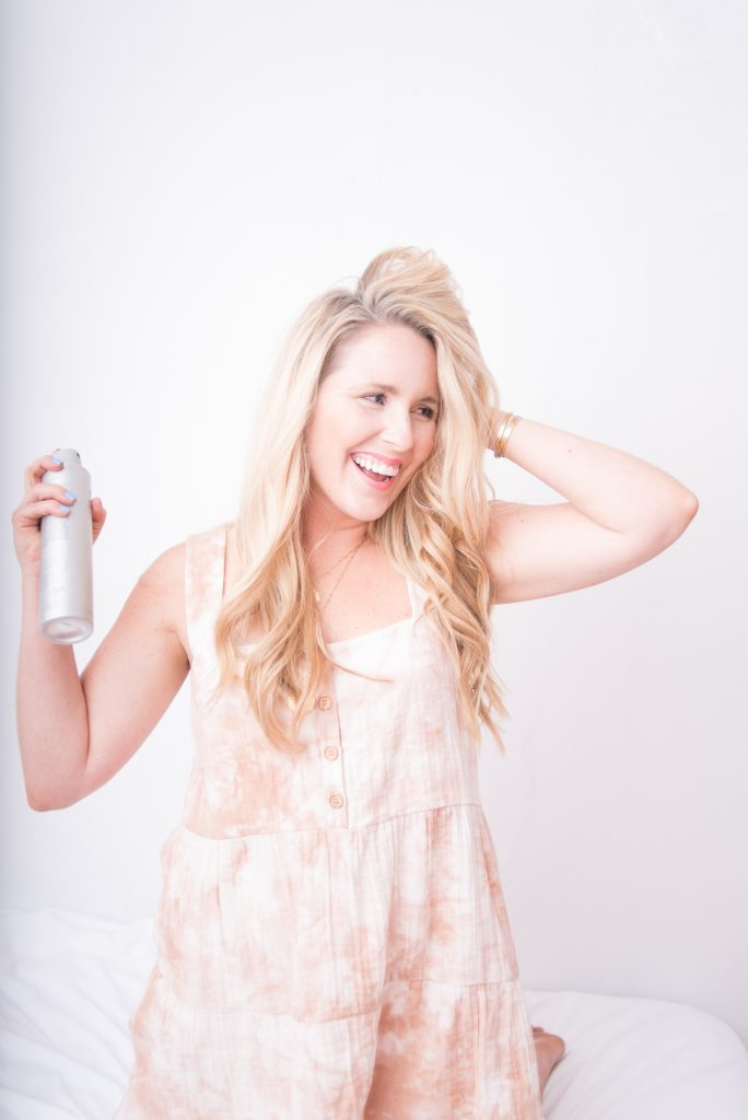 Network Marketing vs Affiliate Marketing by popular Nashville lifestyle blog, Pearls and Twirls: image of a woman kneeling on a bed while using a hair product.
