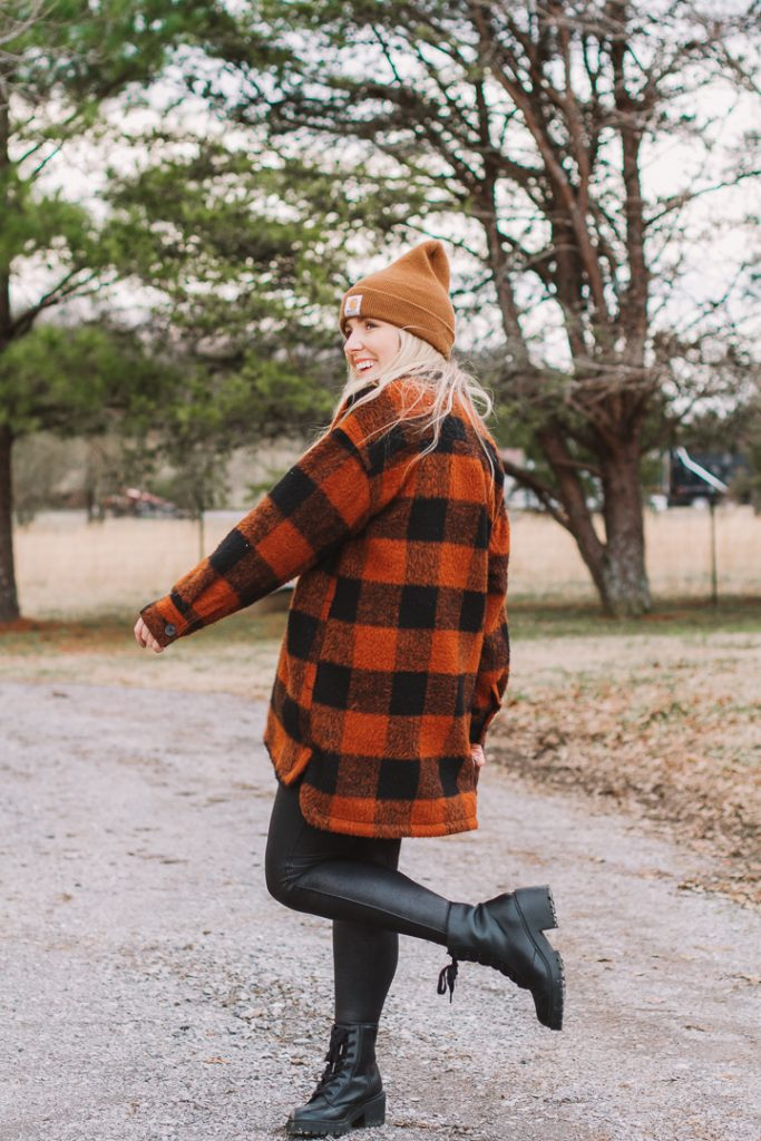 shacket outfit with boots |shacket and leggings outfit | Old Navy Shacket by popular Nashville fashion blog, Pearls and Twirls: image of a woman standing outside on a gravel road and wearing a Carhart beaning, Old Navy orange and black buffalo plaid shacket, black Spanx faux leather leggings, Target combat boots, and My Kind of Lovely swing top.