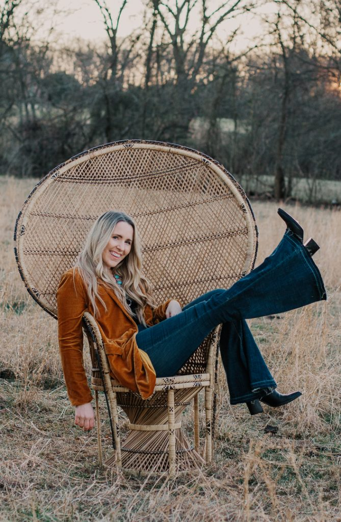 Word of the Year by popular Nashville lifestyle blog, Pearls and Twirls: image of a woman sitting in a Peacock chair and wearing a brown velvet blazer, flare jeans, and black heel ankle boots.