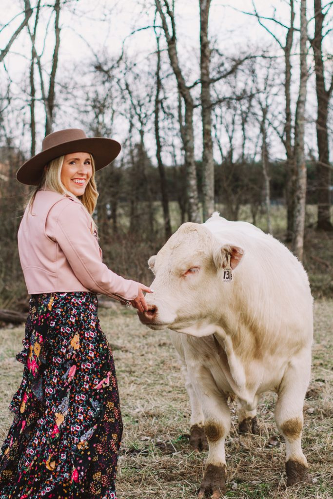 getting unstuck |How to Get Unstuck by popular Nashville lifestyle blog, Pearls and Twirls: image of a woman standing by some white cows and wearing a Charlie 1 Horse felt boater hat, Nuuly pink leather jacket, and Nuuly maxi ruffle floral print skirt.