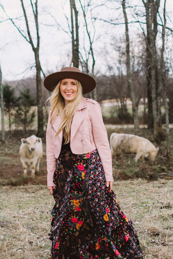 pink jacket and black maxi | How to Get Unstuck by popular Nashville lifestyle blog, Pearls and Twirls: image of a woman standing by some white cows and wearing a Charlie 1 Horse felt boater hat, Nuuly pink leather jacket, and Nuuly maxi ruffle floral print skirt.