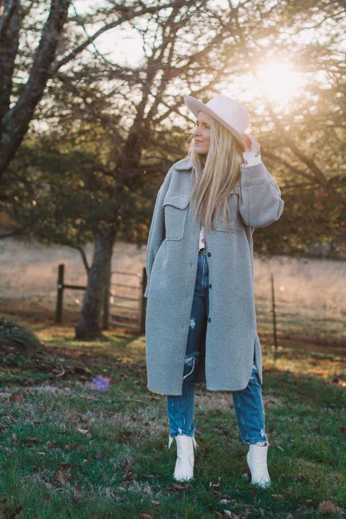 Best Shackets by popular Nashville fashion blog, Pearls and Twirls: image of a woman standing outside and wearing a grey oversized H&M shacket.