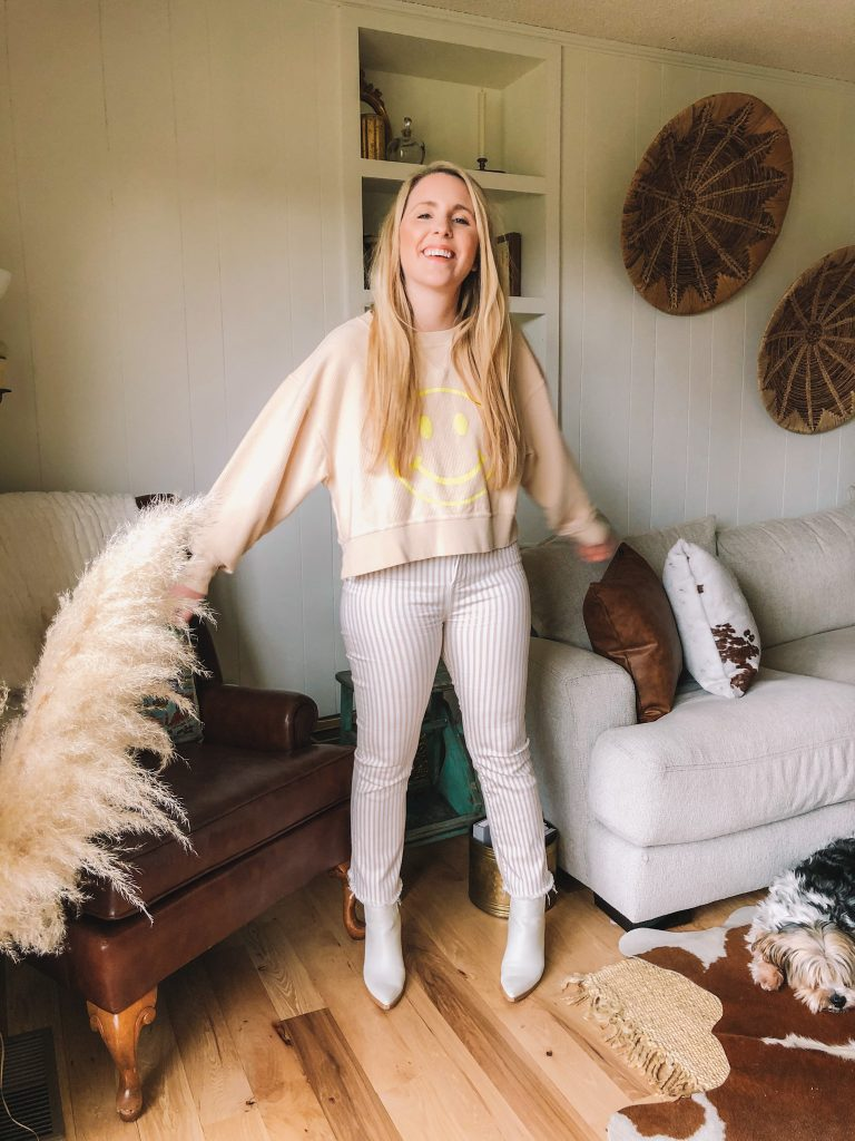 Spring Reset by popular Nashville lifestyle blog, Pearls and Twirls: image of a woman standing in her living room and wearing tan and white stripe pants, white ankle boots, and a tan smily face sweatshirt.