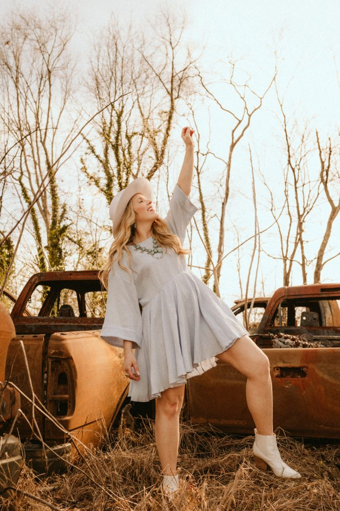 how gratitude reduces stress | Gratitude Reduces Stress by popular Nashville lifestyle blog, Pearls and Twirls: image of a woman wearing a grey dress, white ankle boots, white hat, and turquoise necklace while standing next to some old rusted trucks.