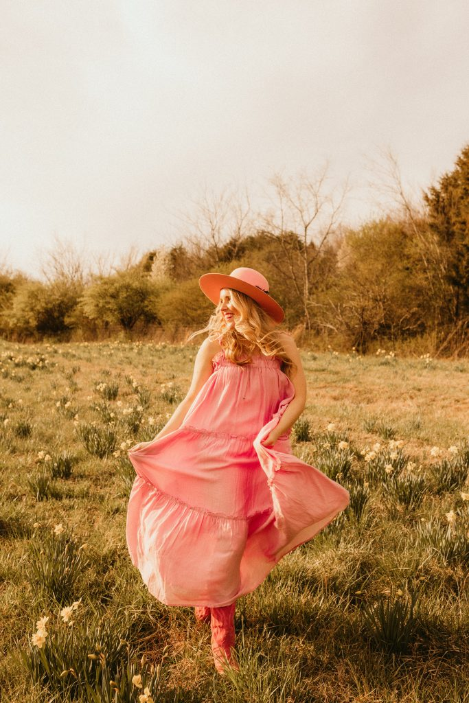 Steps to Achieve Goals by popular Nashville lifestyle blog, Pearls and Twirls: image of a woman wearing a pink maxi dress, pink hat and pink cowboy boots while running through a field.